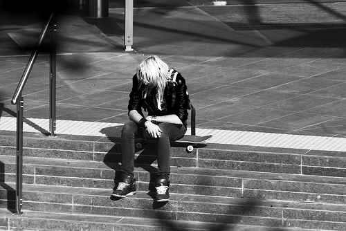 girl - a lonely girl sitting on a sidestreet.