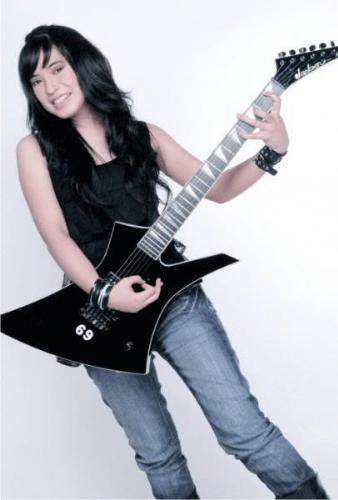 her black shirt and black guitar  - she wearing black shirt and she playing her guitar