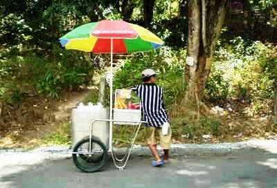 umbrella - a vendor in a cart with wheels and umbrella.