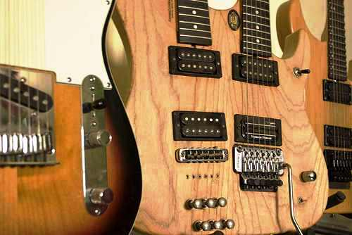 guitar - an unpainted double neck guitar and some others on the left and right of th side of the picture frame shot.