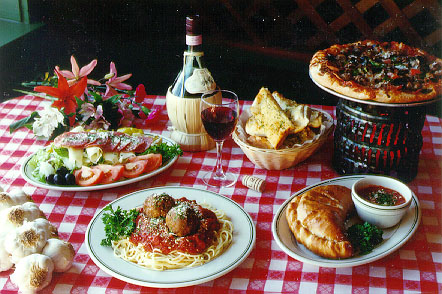 Italian Food - A few dishes of Italian food sitting on a table, such as pizza.