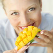 A Westerner is seen here eating a mango with her f - Mango