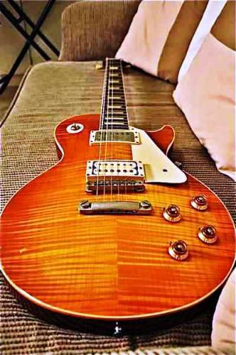 guitar - an orange guitar on a sofa.