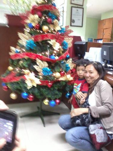 the office tree - this is the office christmas tree..thats my officemate and her son..i cant find other pics of the tree right now..well thats about to change - its looks i mean