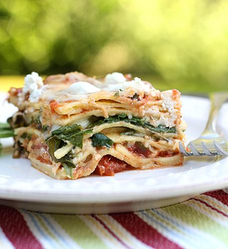 Spinach and Goat Cheese Lasagna - This picture shows a piece of spinach and cheese lasagna. it has lots of tomato sauce and cheese melted over the sides and looks absolutely delicious.