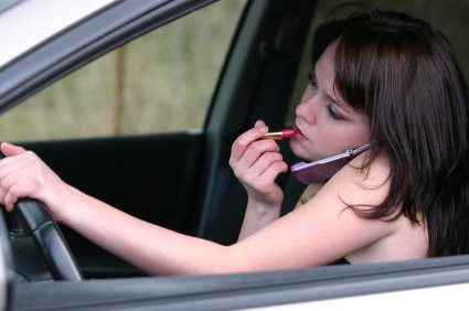 A women doing makeup and talking on cell phone whi - Makeup is most important than life