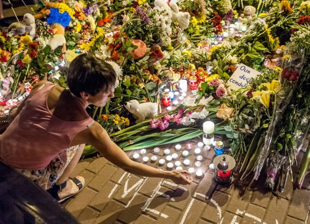 A woman lights a candle outside the Dutch embassy in Kiev. 173 nationals of the Netherlands were on board MH17