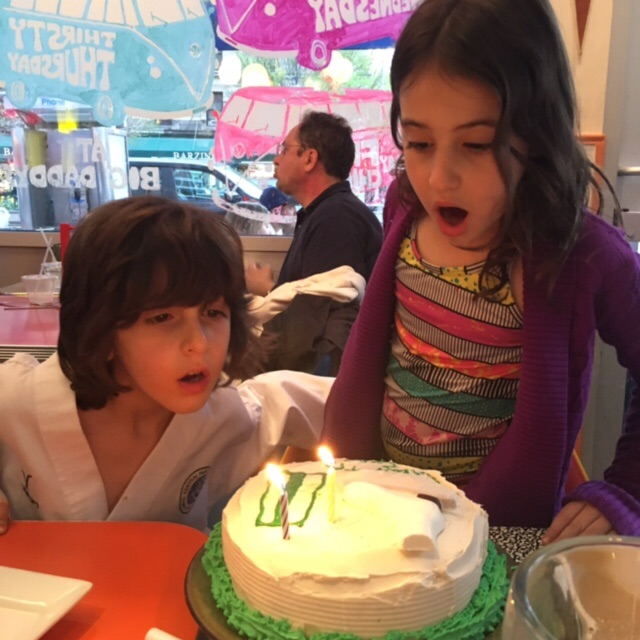 Grandchildren blowing out candles on celebratory cake