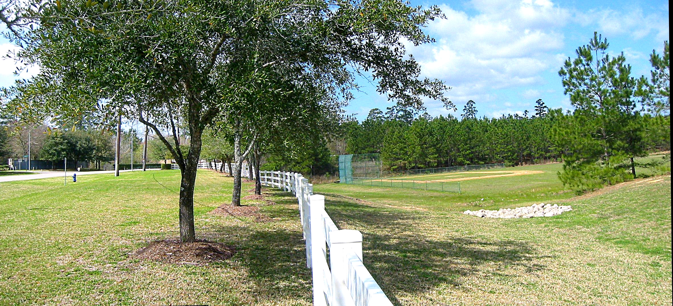 2 Baseball Diamonds Surrounded by a White Wooden Fence - Gus Kilthau