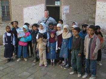 one of my friends in Iraq with the school kids - This is my friend who  is over in Iraq with some of the Iraqi kids that the american soliders have become friends with because they built them a new school