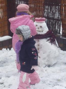 girls and the snowman - my girls standing next to their snowman
