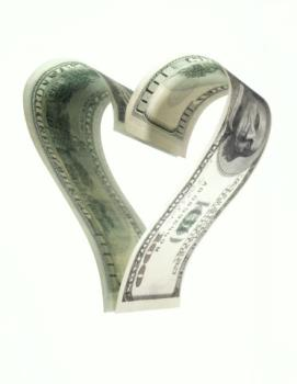 Love of money - Image of two 100 dollar bills curled into a heart.