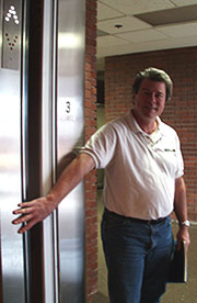 man holding door open - This is a picture of a man holding an elevator door open for someone.