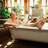 reading - a man reading a magazine while in the bathtub