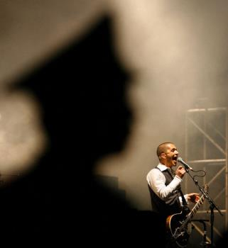 Placebo-2006 Beijing Pop Festival - Placebo's singer Brian Molko on stage as a security guard watches over the crowd during the band's performance at the opening night of the two-day Beijing Pop Festival in China's capital