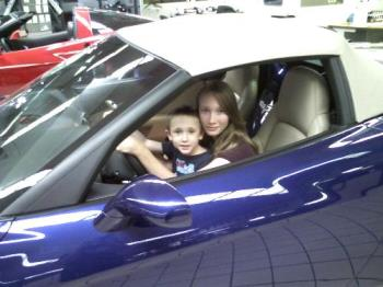 kids in car - This is my eldest daughter and youngest son in a very expensive car in the dealership on display. We got bored. ha ha