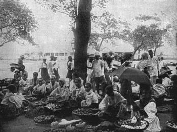 Food Market In Old Cavite - This photograph represents the native fruits, melons, etc., usually found in the markets of the various cities and towns. The stands are generally kept by women amd girls, all of whom smoke cigars and cigarettes.