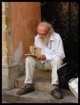 People - A old guy reading a book on the steps of his front door.
