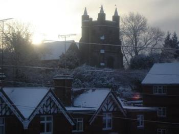 Sun Coming Up Behind The Church In Snow - The winter sun rises behind the church on a snowy morning.