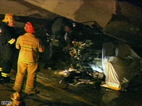 crashed - Firefighters examine the wreckage of a small helicopter that crashed on a California freeway.