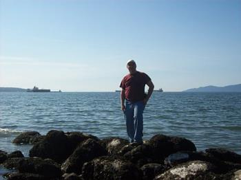 Me standing next to the Pacific Ocean. - This is a picture of me standing on some rocks next to the ocean.