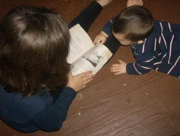 My daughter reading  - Here's my daughter reading a chapter book, and her baby brother coming to check it out.