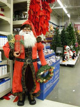 Christmas Shopping with Santa Claus - A photo of Santa Claus standing beside a shop for the Christmas shopping craze.