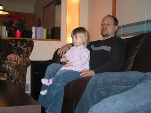 My Older Son teachng Katie how to use the remote - My older son and my granddaughter Katie New Years Eve 2008 at my younger son's place. They are both sports addicts