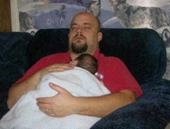 Hubby sleeping with youngest - Hubby is pretending to sleep here, while holding our youngest when he was about a month old.