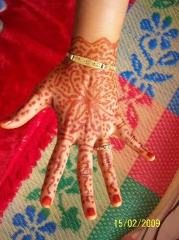 the bride hand is coloured with Inai - Inai is what they call for colouring the bride hand. some colour their feet also