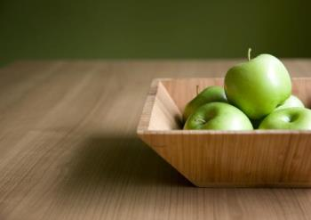 Life needs to be a bit simple - some green apples,a table and a plate are made of woods.That is it.