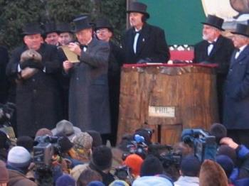 """Groundhog Day - Punxutawney Phil is being held by the man on the left. His """"house"""" is this tree stump, well fake tree stump. Groundhog Day is February 2nd, each year."""