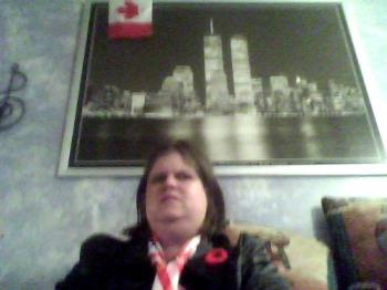 My NY Skyline picture, and me sitting underneath i - You can see my picture in the background. This takes up an entire wall in my apartment. You can also see the top of my long American flag scarf, where it is tied around my neck. I could not get far enough away with the webcam to get more of my scarf ANd the picture, but here you can see a bit of both.