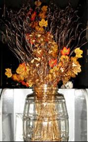 Autumn in a pot - oranges and gold flowers and stems in a crystal vase