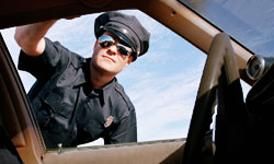 A Cop leaning into a car window to ask for license - This picture depicts the act of issuing a speeding ticket, a curse for office-goers the world over.