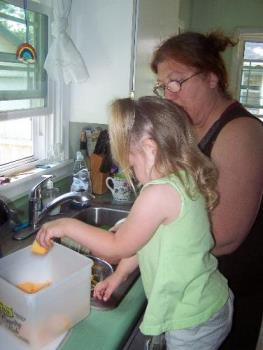 Cutting up cantaloupe - My three year old granddaughter is a real helper bug. We cut up cantaloupe, watermelon and cucumbers this time.