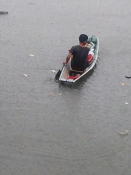 Braving the flood by boat - A man manage to brave the flood by boat. He is out to rescue some families who are up there in their roof waiting for salvation.