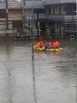 Rescuers on the flooded road - Rescuers braved the flood to rescue the stranded people on top of their roofs.