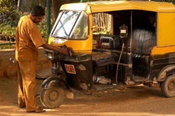 Auto-Rickshaw - Man cleaning his rickshaw early morning.