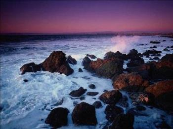 Beautiful beach - Here's a beautiful photo of some waves crashing onto the rocks at a beach during a sunset.
