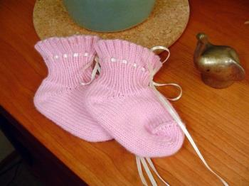Cute pink baby socks - Cute pink baby booty socks lying on a wooden table