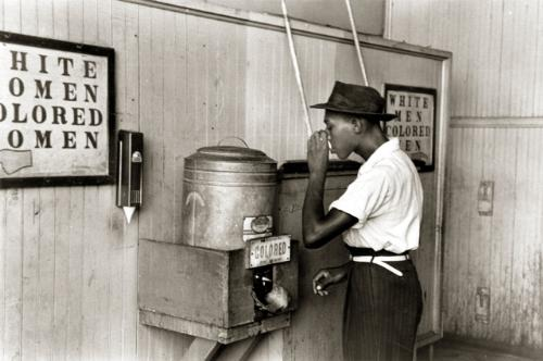 picture of a black man drinking out of a fountain -    this picture was taken after the slavery days were over but before blacks were ever actually able to drink out of the whites water. I hope that no one found this affensive, it wasn't meant to be.