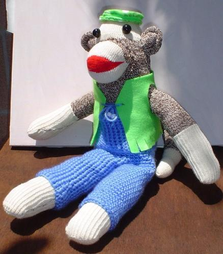 Don't hate me because I'm beautiful. - Sockmonkey with crocheted outfit.