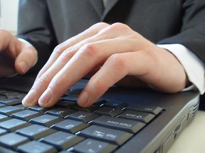 Businessman typing on notepad - A picture of a businessman in a suit and tie typing on a notepad computer. His body language suggests that he is hard at work. I like to imagine that he is writing a business blog.  A royalty-free photo from Stock Xchange, www.sxc.hu