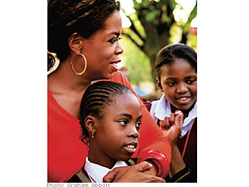 Oprah embracing a South African child - Oprah chooses South Africa for her dream project because she idolizes Nelson Mandela.Here is a photo of Oprah hugging one of the kids in South Africa.