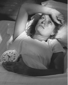 Insomnia - This photo is a woman obviously suffering from insomnia; she is lying in bed, it is clearly late at night, but she is still wide awake.