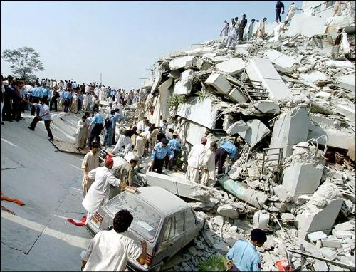 Picture of an earthquake's wake - Earthquake rubble with people scrambling to give help or to look for some help.