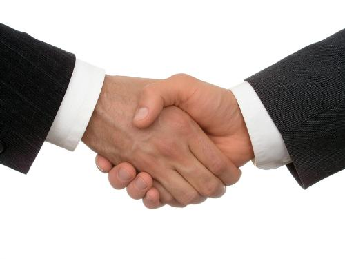 Friendship - A picture of people shaking hands as a sign of friendship.