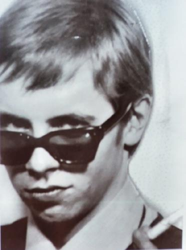 Peekaboo... - This man is playing mysterious with his shades and wry smile.