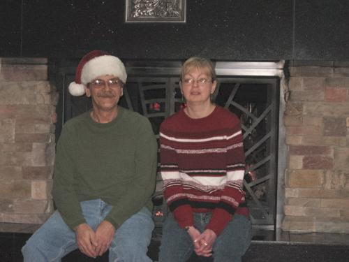 Ahhh So warm - My wife and I sitting on the mantle of the Mystic lake Cainos & Hotel Fireplace. This was in the lobby and taken Christmas Eve Morning.